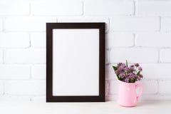Den svarta bruna rammodellen med lilor blommar i prickrosa färger Royaltyfria Bilder