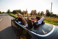 Den svarta cabrioleten är på landsvägen Den lyckliga gruppen av unga flickor och grabbar sitter i bilen rymmer upp deras händer arkivfoto