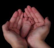 den svarta closeupfoten hands den nyfödda holdingen Arkivbilder