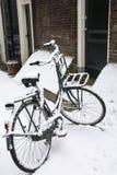 Den svarta cykeln är på jordningen i snö Royaltyfria Bilder