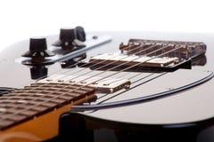 Den svarta elektriska gitarren stränger på en vit bakgrund Royaltyfri Bild