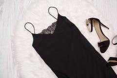 Den svarta enkla klänningen med snör åt och skor på vit päls, ett trendigt begrepp Royaltyfria Foton