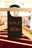 Den svarta etiketten för rabatt 50% som hänger på kläder, rack i lager S Arkivfoto