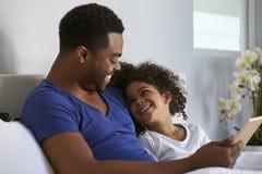 Den svarta fadern och dottern som kopplar av i säng, ser de Royaltyfri Foto