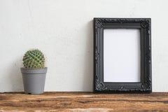 Den svarta fotoramen på den gamla trätabellen med kaktuns över vit lurar Royaltyfria Foton