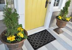 Den svarta gummiellipsdesignen synar hemmet för yttersidan för golvdörren det matta med gula blommor och sidor arkivfoton