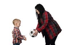 Den svarta haired kvinnan erbjuder en fotbollboll till den lilla pojken Arkivfoto