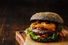 Den svarta hamburgaren med kött- och lökcirklar steker Arkivbilder