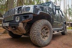 Den svarta Hummer H2 bilen står på den smutsiga vägen Royaltyfria Bilder
