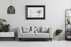 Den svarta industriella bokhyllan och en växt står bredvid en stoppad soffa i en grå vardagsruminre med stället för en kaffeflik royaltyfri fotografi