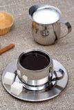 den svarta kanelbruna kaffekoppen mjölkar muffinen Arkivfoton