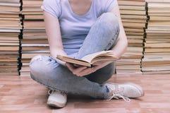 Den svarta katten ligger på golvet bredvid en öppen bok Böcker i bakgrunden Coseup royaltyfria bilder