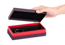 Den svarta klockan i en ask i hand royaltyfri fotografi