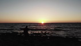 Den svarta konturn av kvinnan på steniga havsstrandhänder fördelade wite under solnedgång över havet med vågor som slår stranden  stock video