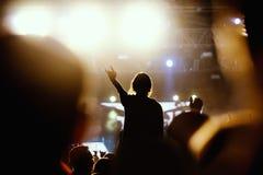 Den svarta konturn av unga flickan vaggar på konsert Arkivfoto
