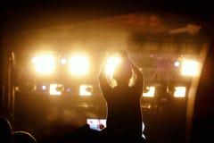Den svarta konturn av unga flickan vaggar på konsert Arkivbild