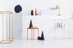 Den svarta kotten, rosa platta, den orange kaffekoppen på metalltabellen på skärm av shoppar med modern konst arkivbild