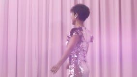 Den svarta kvinnan för det blandade loppet med kort frisyr och lockigt naturligt hår bär den sparkly klänningen för paljetten i r arkivfilmer