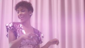 Den svarta kvinnan för det blandade loppet med kort frisyr och lockigt naturligt hår bär den sparkly klänningen för paljetten i r lager videofilmer