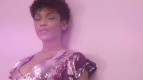 Den svarta kvinnan för det blandade loppet med kort frisyr och lockigt naturligt hår bär den sparkly klänningen för paljetten i r stock video