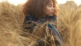 Den svarta kvinnan för det blandade loppet med stort afro lockigt hår i gräsmattafält med för hösthö för höjdpunkten torrt gräs o lager videofilmer