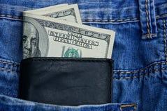 Den svarta läderplånboken ligger i facket av blå byxa Royaltyfri Foto