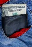 Den svarta läderplånboken ligger i facket av blå röd byxa Royaltyfri Bild