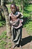 Den svarta Maasai pojken bär på systern för baksida lite Royaltyfri Bild