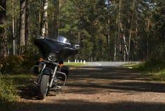 Den svarta motorcykeln körde in i skogen för rekreation Royaltyfri Fotografi