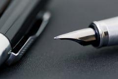 Den svarta pennan med ett lock på en svart bakgrund, affärsidé Arkivbild