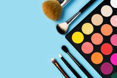 Den svarta plast- paletten av ljust färgad gul, röd, rosa orange ögonskugga och sex sminkborstar av olika typer ordnade arkivbilder