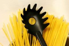 Den svarta plast- spagettiserveren står framme av okokta spagettisugrör royaltyfria foton