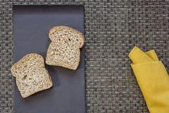 Den svarta plattan med bröd och gulingservetten snedvrider på bakgrund Fotografering för Bildbyråer