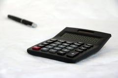 Den svarta räknemaskinen med ut fokuserar den svarta pennan på vit bakgrund Arkivfoto