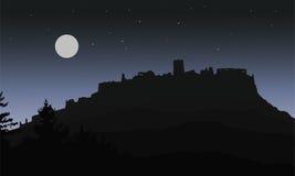Den svarta realistiska konturn av fördärvar av en medeltida slott som byggs på en kulle under natthimlen med en fullmåne och stjä Royaltyfri Fotografi