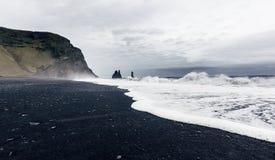 Den svarta sandstranden av Reynisfjara i Island Arkivfoto