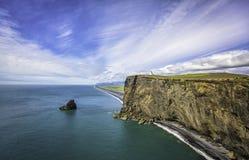 Den svarta sandstranden med fyren på klippan i Island Royaltyfria Bilder