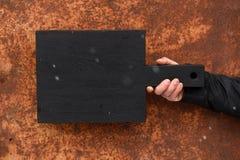 Den svarta skärbrädan som rymdes i hand på anfrätt trä, texturerade backg Arkivbilder