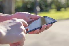 Den svarta smartphonen i hand i parkerar i den öppna luften som tänds av solen royaltyfria foton