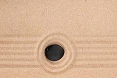 Den svarta stenen ligger i mitten av en cirkel av sand sommar för snäckskal för sand för bakgrundsbegreppsram Royaltyfri Fotografi
