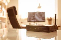 Den svarta trådlösa routeren reflekterade på den vita tabellen i varmt ljus Royaltyfria Bilder