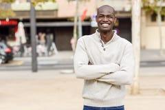 Den svarta unga mannen med armar korsade att le i stads- bakgrund Royaltyfri Fotografi