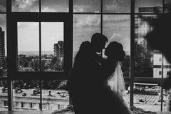 Den svarta vita den fotobruden och brudgummen på bakgrund gör klar fönster Royaltyfri Fotografi