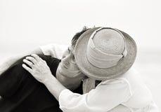 Den svarta vita ledsna modern som rymmer hennes son i besvärade tider, isolerade blek bakgrund royaltyfri foto