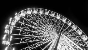 Den svartvita bilden av att rotera upplysta ferris rullar i nöjesfält på natten fotografering för bildbyråer