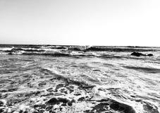 Den svartvita bilden av vågor som kraschar in i, vaggar royaltyfri fotografi