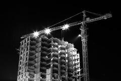 Den svartvita konstruktionsbyggnadsplatsen med tornkranar som bygger under konstruktion, tände med projektorer på Royaltyfria Foton