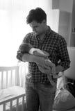 Den svartvita ståenden av den lyckliga fadern som rymmer behandla som ett barn lite Arkivbilder