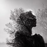 Den svartvita ståenden av en flicka med en dubbel exponering på en bakgrund av trädet krönar Delikat mystisk stående av en kvinna Arkivfoto