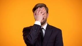 Den svek kontorsarbetaren som g?r framsidan, g?mma i handflatan gesten, orange bakgrund, problem fotografering för bildbyråer